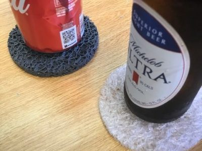beer and can on coasters